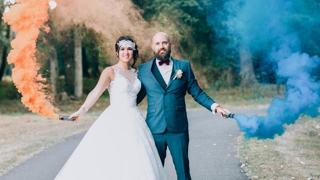 Couple de marie cote à cote avec des fumigènes colorés